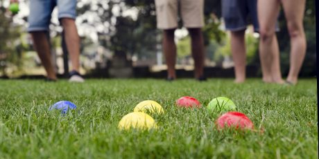 People palying petanque in a park, detail of balls, legs in background.