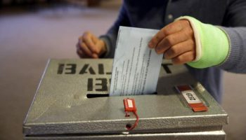 Vote being dropped into ballot box